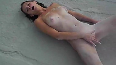 Cute girl masturbating in the sand